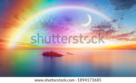 Dusk rainbow concept - Beautiful landscape with multi colored calm sea with double sided rainbow at dusk Royalty-Free Stock Photo #1894173685