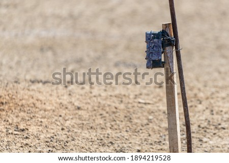 Camera trap on stick. Trail camera for taking a picture of wildlife animal in wild nature.