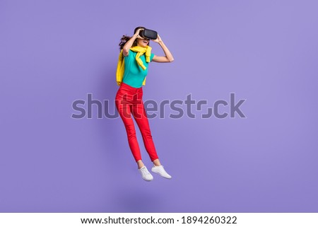 Full length photo of funny wavy young woman dressed pullover shoulders vr eyeglasses jumping isolated purple color background Royalty-Free Stock Photo #1894260322