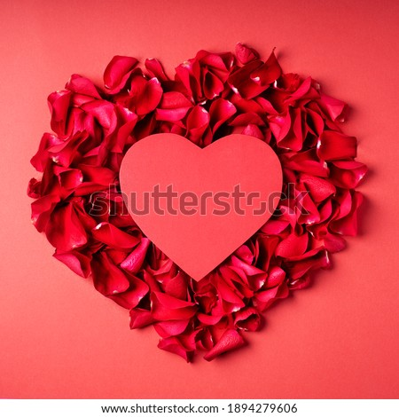 Valentines day greeting card made with red heart paper note and rose petals on red background. Cute love, romantic, wedding or mothers day concept. Flat lay, top view, copy space.