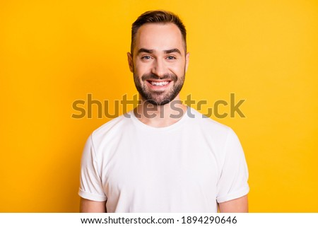 Portrait of attractive cheerful bearded guy freelancer wearing white tshirt isolated over bright yellow color background Royalty-Free Stock Photo #1894290646