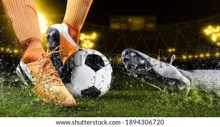 Two football player man in action on dark arena background. Soccer player making sliding tackle Royalty-Free Stock Photo #1894306720