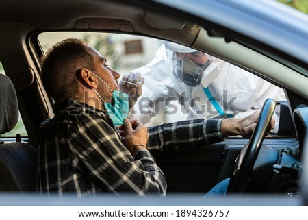 Medical worker performing drive-thru COVID-19 test, taking nasal swab sample from male patient through car window, PCR diagnostic for Coronavirus, doctor in PPE holding test kit. Royalty-Free Stock Photo #1894326757
