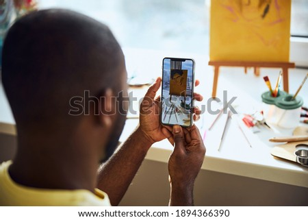 Person taking a photo of a drawing and painting appliances on a cellphone and watching the result