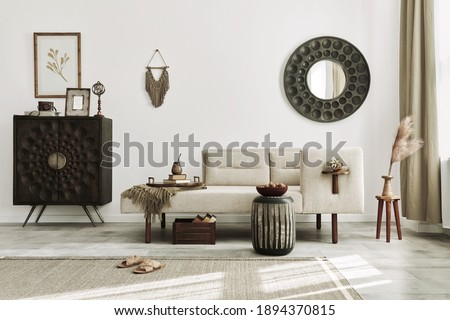Modern ethnic living room interior with design chaise lounge, round mirror, furniture, carpet, decoration, stool and elegant personal accessories. Template. Stylish home decor. Royalty-Free Stock Photo #1894370815