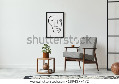 Stylish scandinavian composition of living room with design armchair, black mock up poster frame, plant, wooden stool, book, decoration, loft wall and personal accessories in modern home decor. Royalty-Free Stock Photo #1894377472