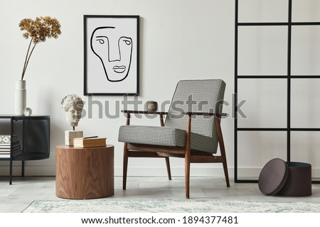 Stylish scandinavian composition of living room with design armchair, black mock up poster frame, commode, wooden stool, book, decoration, loft wall and personal accessories in modern home decor. Royalty-Free Stock Photo #1894377481