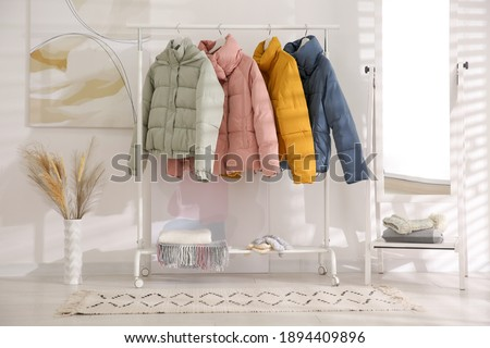 Different warm jackets on rack in stylish room interior Royalty-Free Stock Photo #1894409896