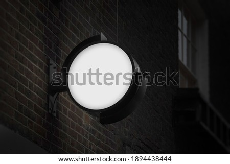 Blank circle sign mockup in the urban environment, on the facade, empty space to display your store sign or logo
