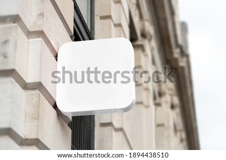 Blank square sign mockup in the urban environment, on the facade, empty space to display your store sign or logo