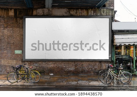 Blank billboard sign mockup in the urban environment, on the facade, empty space to display your advertising or branding campaign