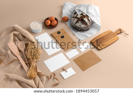 A blank branding set, featuring business cards, envelopes, cards, bread, eggs, flour, serving board, bakery branding mockup, empty space to display your logo or design.