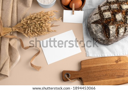 A blank card, with bread, eggs, flour, serving board, bakery branding mockup, empty space to display your logo or design.