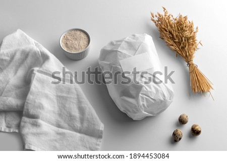 Blank wrapped paper bread with wheat and eggs, bakery branding mockup, empty space to display your logo or design.