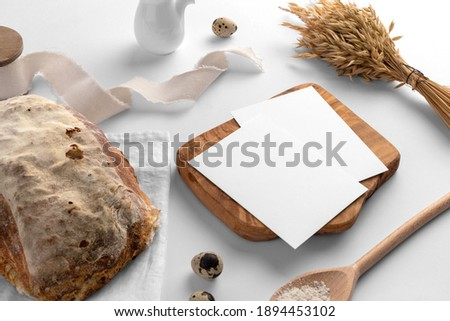 Blank cards on the serving board with bread, bakery branding mockup, empty space to display your logo or design.