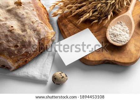 Blank business card on the serving board with bread, bakery branding mockup, empty space to display your logo or design.
