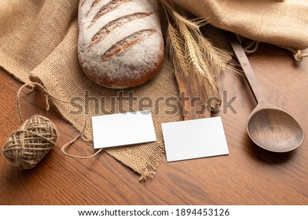 Blank business cards on the wooden background with bread, bakery branding mockup, empty space to display your logo or design.