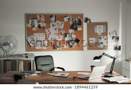 Detective office interior with big wooden desk and evidence board Royalty-Free Stock Photo #1894461259