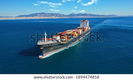 Aerial drone photo of industrial colourful vessel carrying heavy truck size containers cruising the Aegean deep blue sea Royalty-Free Stock Photo #1894474858