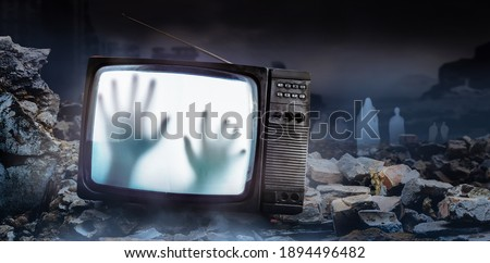 Horror photo of an old black  scary haunted tv set with ghost hands on screen, standing on dark foggy ruined city with spirit figures background.