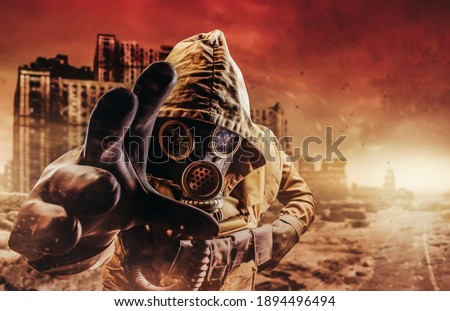 Photo of a stalker in jacket and gloves in damaged gas mask with filter reaching out his hand to camera on destructed apocalyptic wasteland city background. Royalty-Free Stock Photo #1894496494