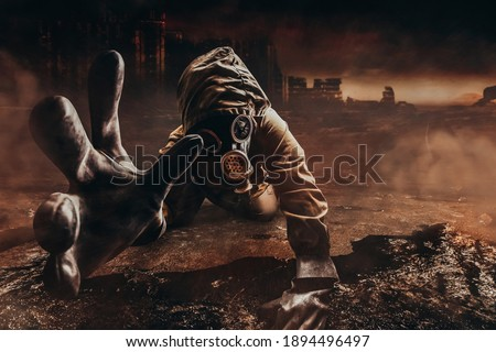 Photo of a dying stalker in jacket and gloves in damaged gas mask with filter reaching out his hand to camera on destructed apocalyptic wasteland city background. Royalty-Free Stock Photo #1894496497
