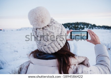 back view of backpacker woman hiking in snowy mountain taking a picture of landscape with mobile phone.winter season. nature and technology