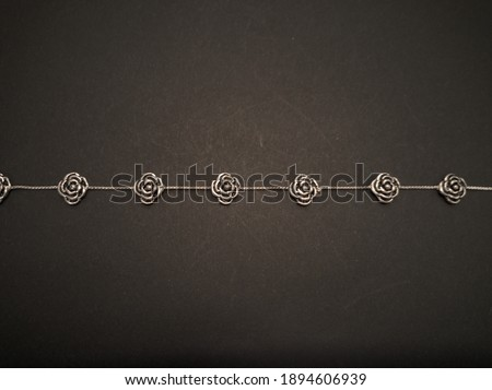 Flat lay with a gothic style silver wristband with rose flowers. Rough background. Gothic subculture and fashion concepts. Copy space. Royalty-Free Stock Photo #1894606939