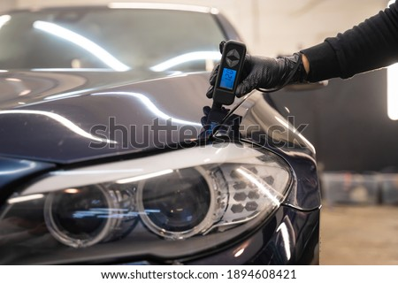 Detailing worker checks the condition of the paintwork with electronic thickness gauge. Car polishing concept Royalty-Free Stock Photo #1894608421
