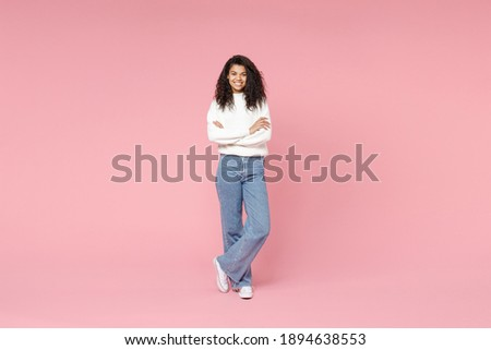 Full length young smiling african american woman 20s curly hair wear white casual knitted sweater jeans looking camera hold hands crossed folded isolated on pastel pink background studio portrait Royalty-Free Stock Photo #1894638553