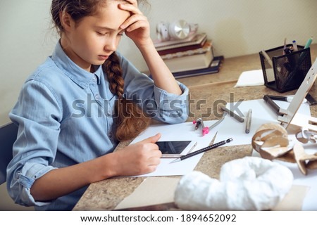 Teenage girl studying online using smartphone, video conferencing, videocall, distance education, learning at home. Girl is drawing sitting at the table. Art, education, creativity, teenage hobbie