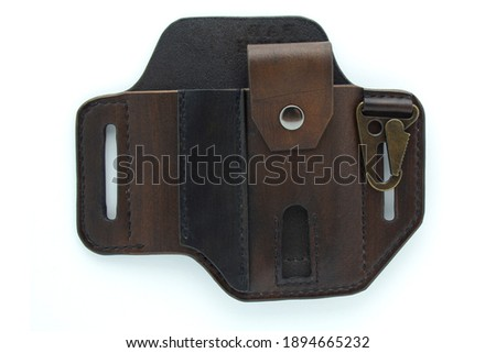 Dark brown custom handmade pancake style leather belt sheath isolated on white background. Leather belt sheath for knife and multi tool. Royalty-Free Stock Photo #1894665232
