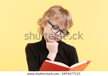 Sad kid. Blond Caucasian nerdy schoolboy in a black sweater, glasses, thinking over an open book. The child is tired of reading the text while doing homework. Isolated on yellow studio background.