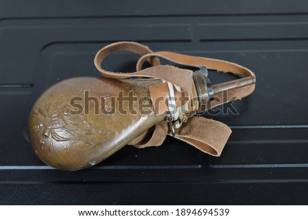 A black powder flask for cap and ball firearms Royalty-Free Stock Photo #1894694539