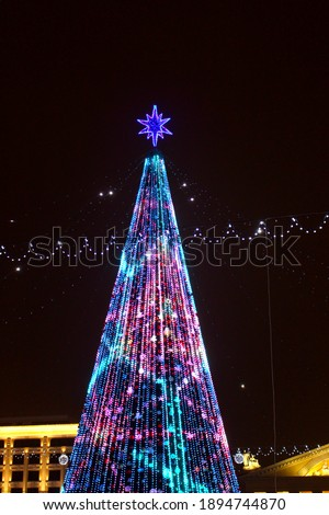View of a festive tree in winter with multi-colored illumination. The central square of Minsk in the new year. Royalty-Free Stock Photo #1894744870