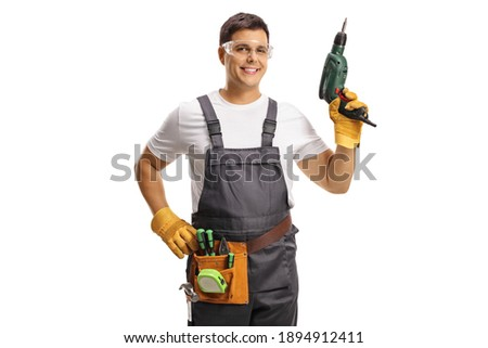 Repairman with protective goggles and a tool belt holding a drill isolated on white background Royalty-Free Stock Photo #1894912411