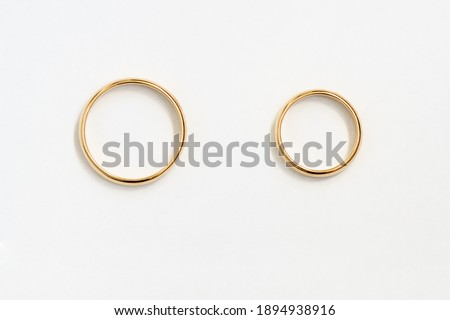 Mr and Mrs bands. Gold rings top view over white paper. For design or drawing.