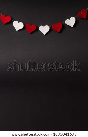 Valentine's day background. Red and white hearts hanging on the string. Copy space