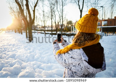 Teenage girl taking pictures in the snow with a smart phone