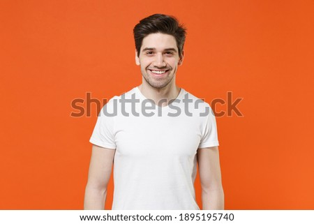 Smiling cheerful funny handsome attractive young man 20s wearing basic casual white blank empty t-shirt standing looking camera isolated on bright orange colour wall background, studio portrait Royalty-Free Stock Photo #1895195740