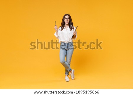 Excited young business woman in white shirt glasses isolated on yellow background. Achievement career wealth business concept. Hold clipboard with papers document, pointing pen up with great new idea