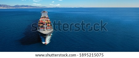 Aerial drone ultra wide photo of huge colourful truck size container tanker vessel cruising deep blue open ocean sea Royalty-Free Stock Photo #1895215075