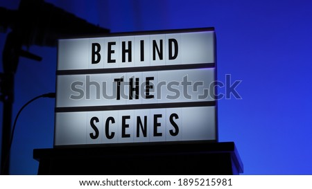 Cinema Light box. Behind the scenes letterboard text on Lightbox. Multi color LED on background. Sillhouette flash snoot hood on tripod. video production studio. Behind the scene Lightbox