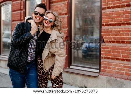Couple of happy people hugging in the city. A man and a woman of European appearance in sunglasses on the street in outerwear. Royalty-Free Stock Photo #1895275975
