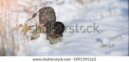 Young woman photographs wildlife in snowy landscape. In a camouflage suit of white color lies in the wedding and waiting wild animal . Banner photo.