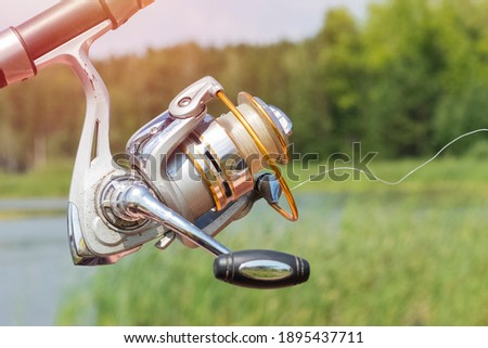 old spinig reel on the background of the lake and forest. spinning detail, close up Royalty-Free Stock Photo #1895437711