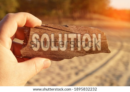 Business and miscellaneous concept. A man holds a sign in his hands - SOLUTION Royalty-Free Stock Photo #1895832232