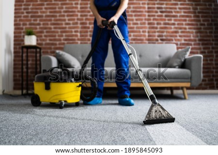 Janitor Cleaning Carpet With Vacuum Cleaner At Home Royalty-Free Stock Photo #1895845093