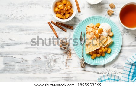 Crepes, thin pancakes with caramelized apple filling and cream fresh. Healthy breakfast in sunny morning . Royalty-Free Stock Photo #1895953369