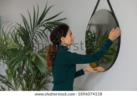 Young Caucasian woman put mirror on wall renovate modern living room in new own home. Millennial female renter or tenant decorate house or apartment moving in or relocating. Rent concept. Royalty-Free Stock Photo #1896074158